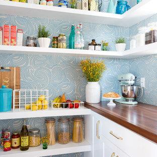 Idées déco pour une arrière-cuisine bord de mer avec un placard à porte shaker, des portes de placard blanches, une crédence bleue et un sol en bois foncé.