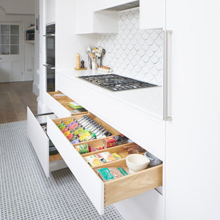 Design ideas for a large contemporary galley separate kitchen in London with an integrated sink, white cabinets, white splashback, stainless steel appliances, porcelain floors and no island.