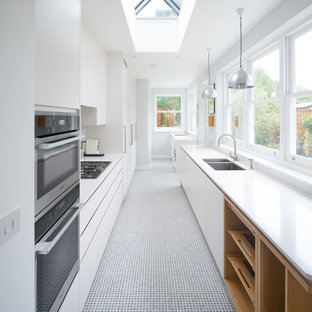 Foto de cocina de galera, contemporánea, grande, cerrada, sin isla, con fregadero integrado, puertas de armario blancas, salpicadero blanco, electrodomésticos de acero inoxidable y suelo de baldosas de porcelana