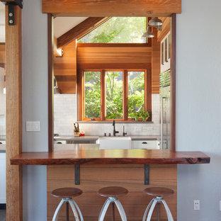 サンフランシスコの中サイズのエクレクティックスタイルのおしゃれなキッチン (エプロンフロントシンク、シェーカースタイル扉のキャビネット、白いキャビネット、人工大理石カウンター、白いキッチンパネル、サブウェイタイルのキッチンパネル、シルバーの調理設備の、無垢フローリング、茶色い床、グレーのキッチンカウンター) の写真