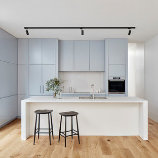 Inspiration for a small modern galley kitchen in Melbourne with a double-bowl sink, flat-panel cabinets, blue cabinets, white splashback, light hardwood floors, with island, white benchtop, panelled appliances and beige floor.