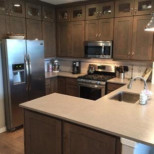 デンバーの大きいラスティックスタイルのおしゃれなキッチン (アンダーカウンターシンク、シェーカースタイル扉のキャビネット、中間色木目調キャビネット、珪岩カウンター、白いキッチンパネル、セラミックタイルのキッチンパネル、シルバーの調理設備の、リノリウムの床) の写真
