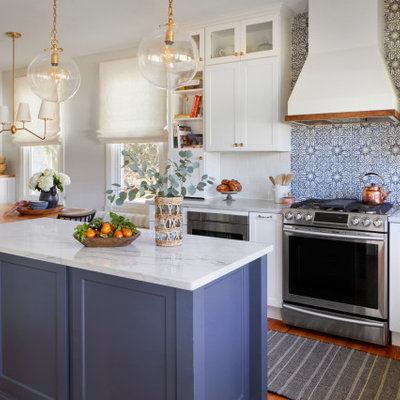 Eat-in kitchen - large country medium tone wood floor and brown floor eat-in kitchen idea in Philadelphia with a farmhouse sink, shaker cabinets, white cabinets, quartzite countertops, white backsplash, terra-cotta backsplash, stainless steel appliances, an island and white countertops
