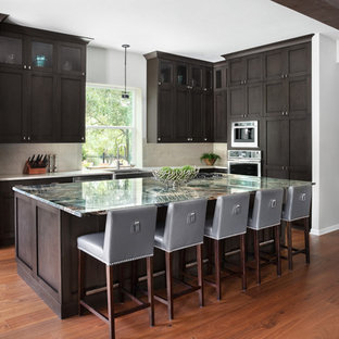 Large industrial single-wall eat-in kitchen in Austin with a farmhouse sink, shaker cabinets, dark wood cabinets, granite benchtops, beige splashback, porcelain splashback, stainless steel appliances, medium hardwood floors, with island, brown floor and green benchtop.