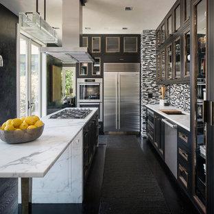 シアトルのインダストリアルスタイルのおしゃれなキッチン (アンダーカウンターシンク、大理石カウンター、シルバーの調理設備、濃色無垢フローリング、ガラス扉のキャビネット、黒いキャビネット、マルチカラーのキッチンパネル、ボーダータイルのキッチンパネル、黒い床) の写真