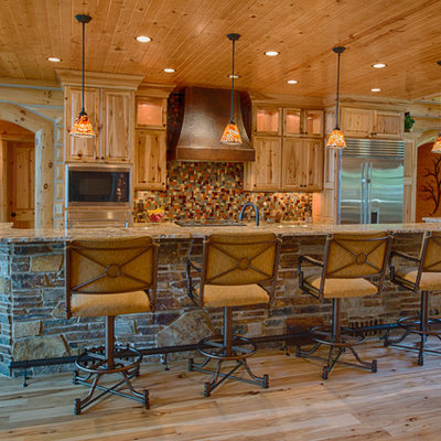 Mountain style kitchen photo in Other with raised-panel cabinets, medium tone wood cabinets, multicolored backsplash and stainless steel appliances