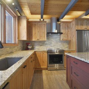 ポートランドの中サイズのラスティックスタイルのおしゃれなキッチン (シングルシンク、シェーカースタイル扉のキャビネット、中間色木目調キャビネット、御影石カウンター、ベージュキッチンパネル、石タイルのキッチンパネル、シルバーの調理設備の、ラミネートの床、茶色い床、ベージュのキッチンカウンター) の写真