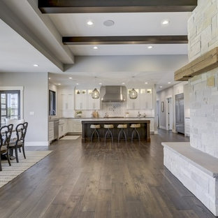 Design ideas for a large farmhouse u-shaped open plan kitchen in Chicago with a belfast sink, recessed-panel cabinets, white cabinets, engineered stone countertops, white splashback, metro tiled splashback, stainless steel appliances, porcelain flooring, an island, brown floors and white worktops.