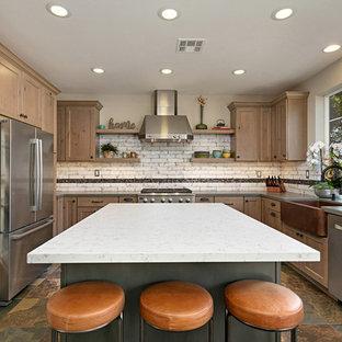 サンディエゴの中サイズのラスティックスタイルのおしゃれなキッチン (エプロンフロントシンク、シェーカースタイル扉のキャビネット、中間色木目調キャビネット、クオーツストーンカウンター、白いキッチンパネル、磁器タイルのキッチンパネル、シルバーの調理設備の、スレートの床、マルチカラーの床、グレーのキッチンカウンター) の写真