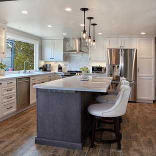 Mid-sized transitional open concept kitchen appliance - Mid-sized transitional l-shaped porcelain floor and brown floor open concept kitchen photo in Orange County with an undermount sink, recessed-panel cabinets, white cabinets, quartz countertops, gray backsplash, marble backsplash, stainless steel appliances, an island and white countertops