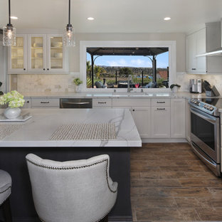 Inspiration for a mid-sized eclectic l-shaped open plan kitchen in Orange County with an undermount sink, recessed-panel cabinets, white cabinets, quartz benchtops, grey splashback, marble splashback, stainless steel appliances, porcelain floors, with island, brown floor and white benchtop.