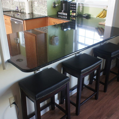 Example of a small trendy u-shaped linoleum floor eat-in kitchen design in Baltimore with an undermount sink, raised-panel cabinets, medium tone wood cabinets, granite countertops, green backsplash, glass tile backsplash, stainless steel appliances and a peninsula