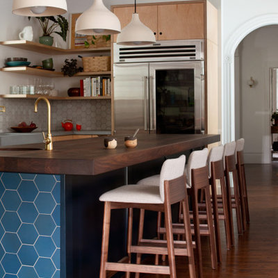 Trendy l-shaped brown floor and medium tone wood floor eat-in kitchen photo in San Francisco with a farmhouse sink, flat-panel cabinets, light wood cabinets, concrete countertops, white backsplash, ceramic backsplash, stainless steel appliances, an island and gray countertops