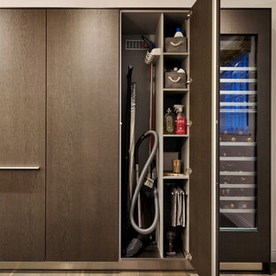 Design ideas for a large contemporary galley separate kitchen in Devon with an integrated sink, flat-panel cabinets, dark wood cabinets, stainless steel benchtops, white splashback, subway tile splashback, porcelain floors, with island and stainless steel appliances.