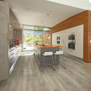 ロサンゼルスの広いコンテンポラリースタイルのおしゃれなII型キッチン (ドロップインシンク、フラットパネル扉のキャビネット、黒いキャビネット、大理石カウンター、シルバーの調理設備、無垢フローリング、オレンジのキッチンカウンター) の写真