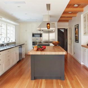 Diseño de cocina clásica renovada con fregadero integrado, armarios estilo shaker, puertas de armario blancas, encimera de acero inoxidable, salpicadero de vidrio, electrodomésticos de acero inoxidable, suelo de madera en tonos medios y una isla