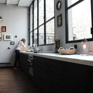 Ejemplo de cocina lineal, retro, grande, abierta, con puertas de armario negras, encimera de mármol, salpicadero blanco, electrodomésticos con paneles y suelo de madera oscura