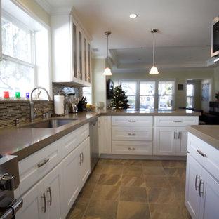 Geschlossene, Mittelgroße Moderne Küche in L-Form mit Unterbauwaschbecken, Schrankfronten im Shaker-Stil, weißen Schränken, Kalkstein-Arbeitsplatte, bunter Rückwand, Rückwand aus Stäbchenfliesen, Küchengeräten aus Edelstahl, Schieferboden, Kücheninsel und braunem Boden in Los Angeles