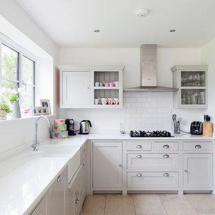 サリーの中くらいのカントリー風おしゃれなキッチン (エプロンフロントシンク、シェーカースタイル扉のキャビネット、グレーのキャビネット、白いキッチンパネル、サブウェイタイルのキッチンパネル、シルバーの調理設備、人工大理石カウンター、ライムストーンの床、アイランドなし) の写真