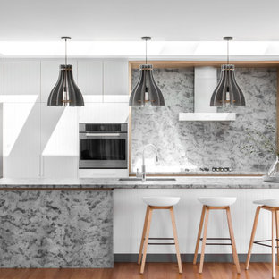 Inspiration for a contemporary galley open plan kitchen in Hobart with white cabinets, granite benchtops, stainless steel appliances, grey benchtop, flat-panel cabinets, grey splashback, medium hardwood floors, with island and brown floor.