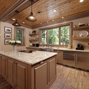ワシントンD.C.のカントリー風おしゃれなキッチン (レイズドパネル扉のキャビネット、茶色いキャビネット、ベージュのキッチンカウンター、エプロンフロントシンク、ベージュキッチンパネル、シルバーの調理設備の、茶色い床) の写真