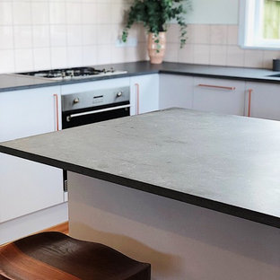 This is an example of a midcentury kitchen in Auckland with an undermount sink, grey cabinets, quartz benchtops, pink splashback, ceramic splashback, stainless steel appliances and with island.