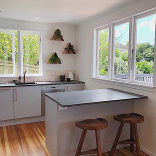 This is an example of a midcentury open plan kitchen in Auckland with an undermount sink, grey cabinets, quartz benchtops, pink splashback, ceramic splashback, stainless steel appliances and medium hardwood floors.