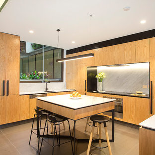 Large contemporary u-shaped open plan kitchen in Sydney with marble splashback, panelled appliances, with island, flat-panel cabinets, medium wood cabinets, white splashback, grey floor, an undermount sink, quartz benchtops, porcelain floors and white benchtop.