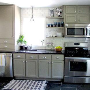 デトロイトの小さいエクレクティックスタイルのおしゃれなI型キッチン (アンダーカウンターシンク、落し込みパネル扉のキャビネット、ベージュのキャビネット、御影石カウンター、黄色いキッチンパネル、サブウェイタイルのキッチンパネル、シルバーの調理設備の、スレートの床、アイランドなし、黒い床) の写真