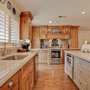 Foto på ett vintage kök, med en undermonterad diskho, luckor med upphöjd panel, beige skåp, rostfria vitvaror och stänkskydd i skiffer