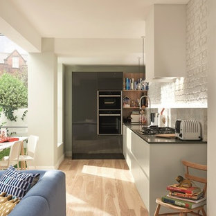 Mid-sized industrial single-wall open plan kitchen in Dublin with an integrated sink, flat-panel cabinets, black cabinets, quartzite benchtops, white splashback, marble splashback, coloured appliances, laminate floors, no island and brown floor.