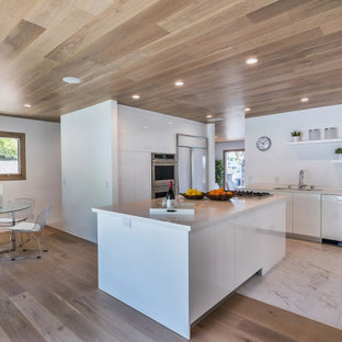 This is an example of a mid-sized midcentury l-shaped kitchen pantry in Los Angeles with flat-panel cabinets, white cabinets, white splashback, with island, white floor and white benchtop.
