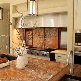 シーダーラピッズの大きいモダンスタイルのおしゃれなキッチン (アンダーカウンターシンク、シェーカースタイル扉のキャビネット、中間色木目調キャビネット、御影石カウンター、茶色いキッチンパネル、石スラブのキッチンパネル、シルバーの調理設備、磁器タイルの床) の写真