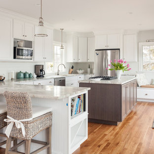 Inspiration for a beach style u-shaped medium tone wood floor kitchen remodel in Boston with white cabinets and an island