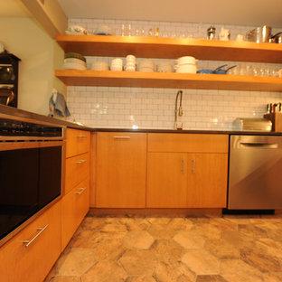 クリーブランドの広いインダストリアルスタイルのおしゃれなキッチン (アンダーカウンターシンク、フラットパネル扉のキャビネット、中間色木目調キャビネット、御影石カウンター、白いキッチンパネル、サブウェイタイルのキッチンパネル、シルバーの調理設備) の写真