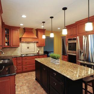 Große Klassische Küche in L-Form mit Unterbauwaschbecken, Schrankfronten mit vertiefter Füllung, hellbraunen Holzschränken, Granit-Arbeitsplatte, Rückwand aus Zementfliesen, Küchengeräten aus Edelstahl, Backsteinboden und Kücheninsel in Cleveland