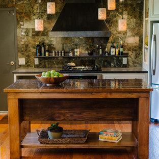 Inredning av ett klassiskt l-kök, med grönt stänkskydd, rostfria vitvaror och bänkskiva i akrylsten