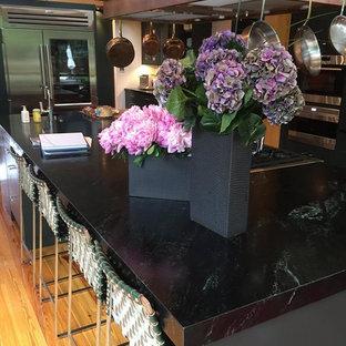 Réalisation d'une cuisine américaine style shabby chic de taille moyenne avec un évier de ferme, un placard à porte plane, des portes de placard noires, un plan de travail en stéatite, une crédence blanche, un électroménager en acier inoxydable, un sol en bois brun et un îlot central.