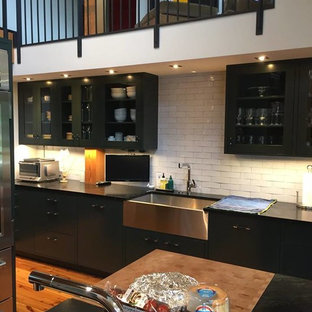 Design ideas for a mid-sized shabby-chic style eat-in kitchen in Denver with a farmhouse sink, flat-panel cabinets, black cabinets, soapstone benchtops, white splashback, stainless steel appliances, medium hardwood floors and with island.