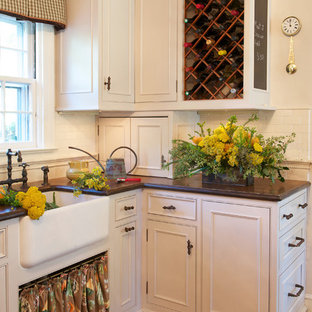 This is an example of a large country u-shaped eat-in kitchen in Other with a farmhouse sink, beaded inset cabinets, white cabinets, medium hardwood floors, no island, copper benchtops, white splashback, subway tile splashback and stainless steel appliances.