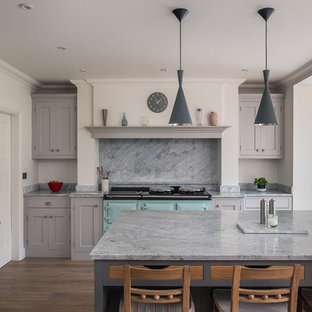 Photo of a large traditional u-shaped kitchen/diner in Surrey with a belfast sink, grey cabinets, marble worktops, grey splashback, stone slab splashback, integrated appliances, medium hardwood flooring, an island and shaker cabinets.