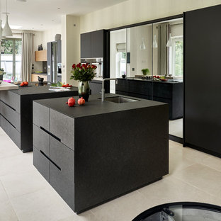Contemporary kitchen in Surrey with a submerged sink, flat-panel cabinets, black cabinets, black appliances and multiple islands.