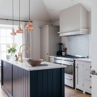 Mid-sized coastal kitchen pictures - Kitchen - mid-sized coastal galley medium tone wood floor and brown floor kitchen idea in Cornwall with a farmhouse sink, gray cabinets, solid surface countertops, blue backsplash, ceramic backsplash, stainless steel appliances, an island and white countertops