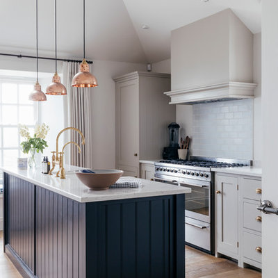 Kitchen - mid-sized coastal galley medium tone wood floor and brown floor kitchen idea in Cornwall with a farmhouse sink, gray cabinets, solid surface countertops, blue backsplash, ceramic backsplash, stainless steel appliances, an island and white countertops