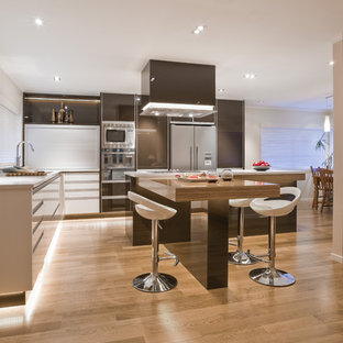 Example of a large trendy l-shaped light wood floor eat-in kitchen design in Los Angeles with flat-panel cabinets, brown cabinets, stainless steel appliances, an undermount sink and an island