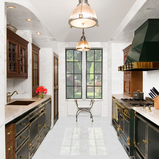 Design ideas for a mid-sized traditional galley separate kitchen in Austin with an undermount sink, dark wood cabinets, marble benchtops, white splashback, stone tile splashback, marble floors, no island, glass-front cabinets, black appliances and white floor.