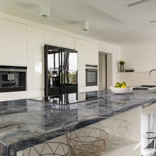 Foto de cocina moderna, abierta, con fregadero bajoencimera, puertas de armario blancas, encimera de cuarcita, electrodomésticos negros, suelo de baldosas de porcelana, una isla, suelo negro y encimeras azules