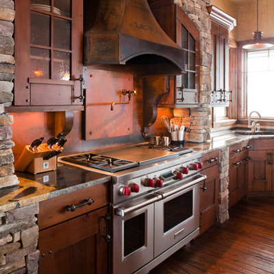 Mountain style l-shaped kitchen photo in Denver with an undermount sink, dark wood cabinets, granite countertops, brown backsplash, metal backsplash, stainless steel appliances and shaker cabinets