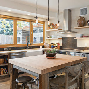 This is an example of a mid-sized u-shaped eat-in kitchen in Denver with a farmhouse sink, open cabinets, distressed cabinets, quartz benchtops, metallic splashback, stainless steel appliances, light hardwood floors, with island, beige floor and grey benchtop.
