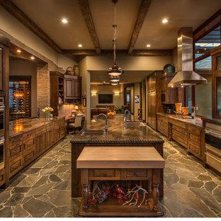 Immagine di una grande cucina rustica con lavello sottopiano, ante con finitura invecchiata, top in marmo, paraspruzzi con piastrelle in pietra, elettrodomestici in acciaio inossidabile e isola